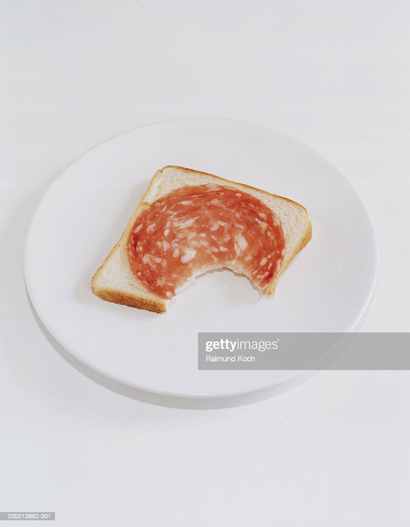 Bite taken out of salami on piece of bread : Stock Photo