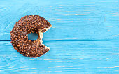 Delicious bitten chocolate donut on an empty wooden background