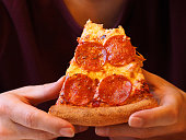 Bitten slice of pizza in the hands of the person close-up. The man in a purple T-shirt with well-groomed hands is eating pepperoni pizza