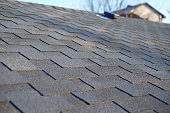 Bitumen tile roof. Roof Shingles - Roofing. Close up view on Asphalt Roofing Shingles .