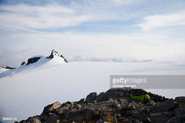 A bivy sac sits alone on a rock outcrop on an empty glacier with a jagged mountain in the distance.