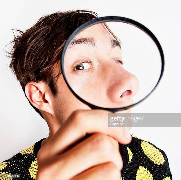 Bizarre boy examining face through magnifying glass