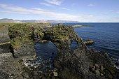 Bizarre Felsformationen in Torbogenform und Kliff aus vulkanischem Basaltgestein an der Meereskueste auf der Suedseite der Halbinsel Snaefellsnes in...