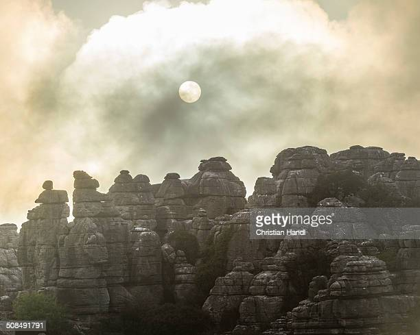 Bizarre limestone rock formations with the sun and fog, El Torcal Nature Reserve, Antequera, Andalusia, Spain