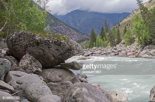 Bizarre stone on the shore of a mountain river. : Stock Photo