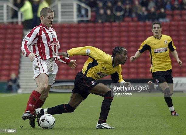 Bjani Gudjonsson of Stoke City tackles Danny Thomas of Bournemouth during the FA Cup Fourth Round game between Stoke City and AFC Bournemouth at...