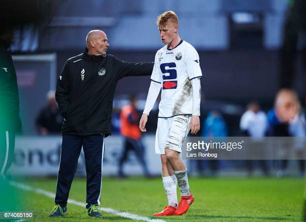 Bjarke Jacobsen of Vendsyssel FF walks off the pitch after receiving a red card from referee Michael Tykgaard and is received by Erik Rasmussen head...