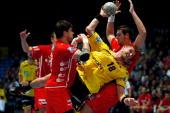 Bjarte Myrhol of RheinNeckar Loewen is challenged by Nenad Vuckovic and Felix Danner of Melsungen during the Toyota Handball Bundesliga match between...