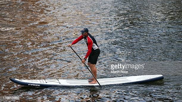 Bjoern Dunkerbeck former surf world champion competes during the Stand Up Paddling celebrity race at Magellan Terassen on August 16 2013 in Hamburg...