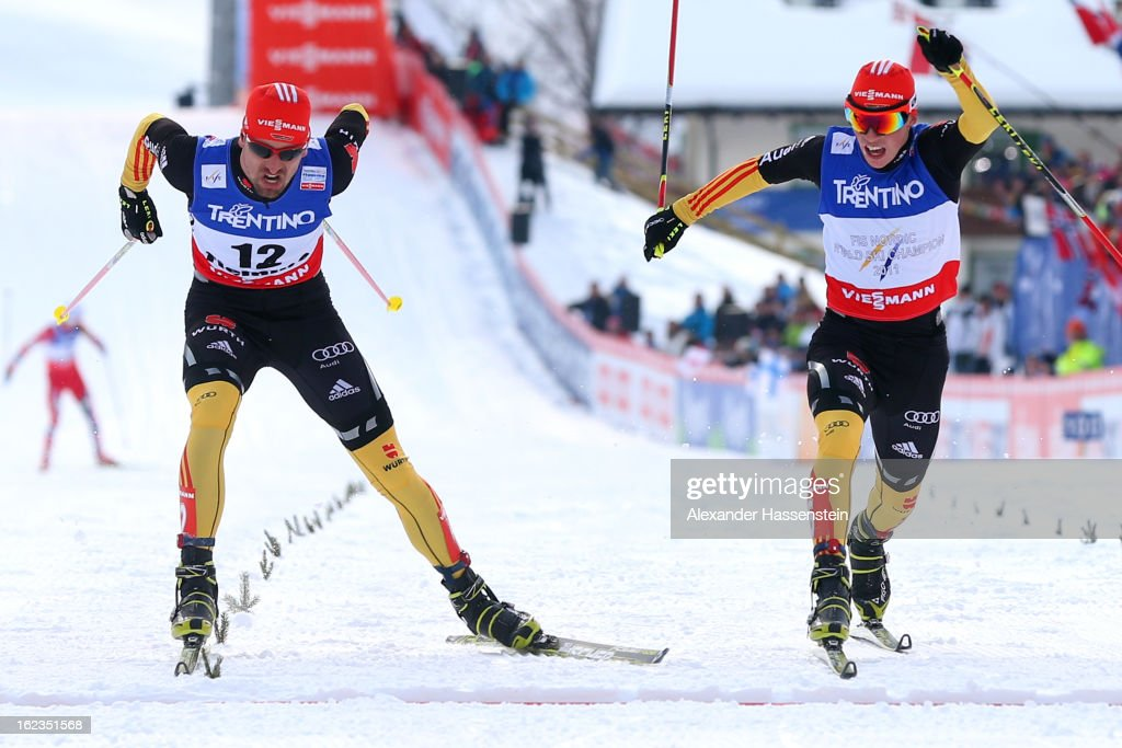Bjoern Kircheisen (L) of Germany crosses the finish line ahead of his team mate <a gi-track='captionPersonalityLinkClicked' href=/galleries/search?phrase=Eric+Frenzel&family=editorial&specificpeople=4595984 ng-click='$event.stopPropagation()'>Eric Frenzel</a> during the Men's Nordic Combined on February 22, 2013 in Val di Fiemme, Italy.