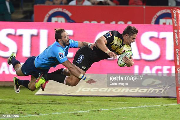 Bjorn Basson of the Bulls can't stop Rohan Janse van Rensburg of the Lions from scoring during the Super Rugby match between the Vodacom Bulls and...