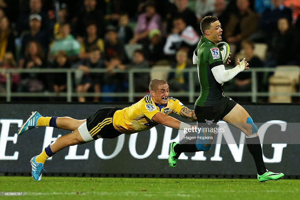 Bjorn Basson of the Bulls is tackled by TJ Perenara of the Hurricanes during the round eight Super Rugby match between the Hurricanes and the Bulls...