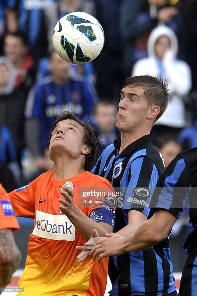 Bjorn Engels of Club Brugge battles for the ball with Jelle Vossen of KRC Genk during the Jupiler Pro League match between Club Brugge KV and KRC Genk on October 27, 2013 in Brugge, Belgium.