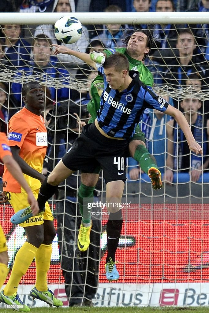 Bjorn Engels of Club Brugge battles for the ball with Laszlo Koteles of KRC Genk during the Jupiler Pro League match between Club Brugge KV and KRC Genk on October 27, 2013 in Brugge, Belgium.