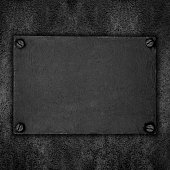 black steel plate with screws on abstract rough background