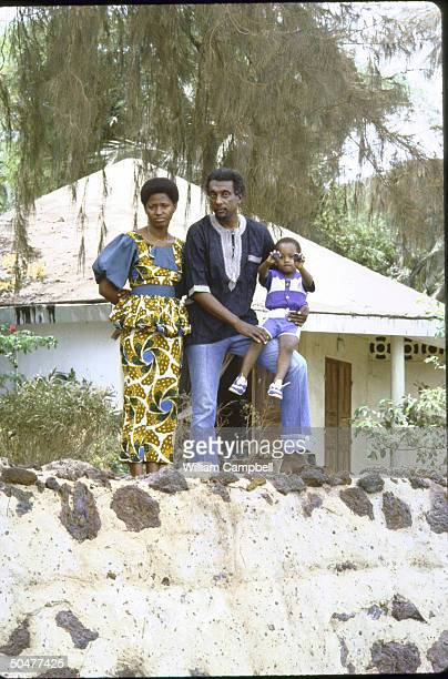 Black activist Stokely Carmichael aka Kwame Ture w wife Marlyatou Barry son Boca Biro in yard at home