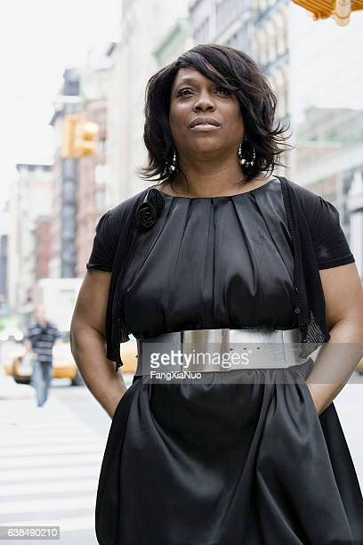 Black adult woman looking ahead in downtown city