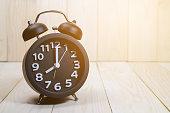 Black alarm clock  on wood background / vintage tone