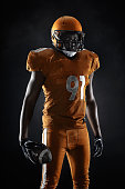 Black American football player on dark background.  A muscular sportsman dressed in an orange professional uniform for American football
