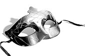 Black and gray masquerade mask against white background