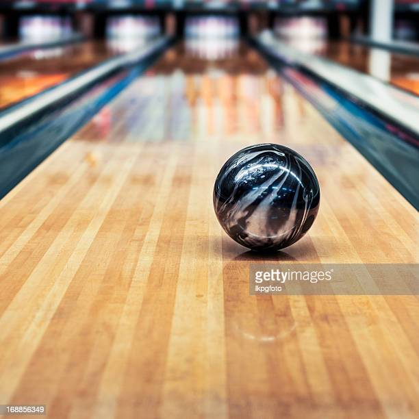 A black and silver bowling ball rolling down the lane