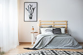 Black and white bedroom with grey accessories, big window and cactus poster