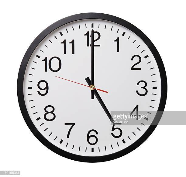 Black and white clock showing five o'clock