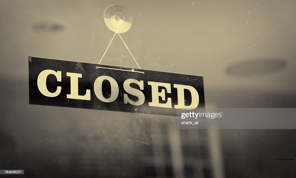 Black and white closeup of a Closed sign hanging on a window