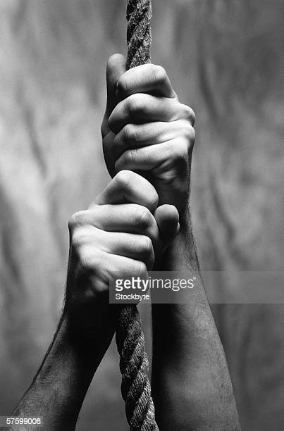 black and white close-up of hands gripping a hung rope