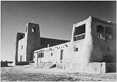 A black and white exterior photograph of San Estevan del Rey Mission Church the adobe building was constructed in the 17th century wooden beams that...