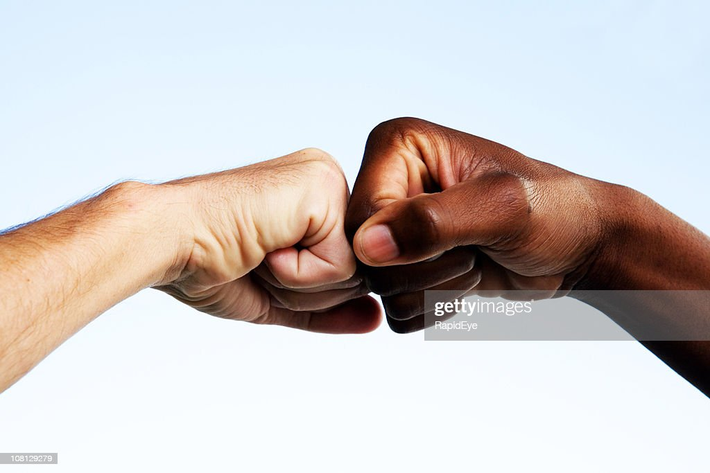 Black and white fists touching
