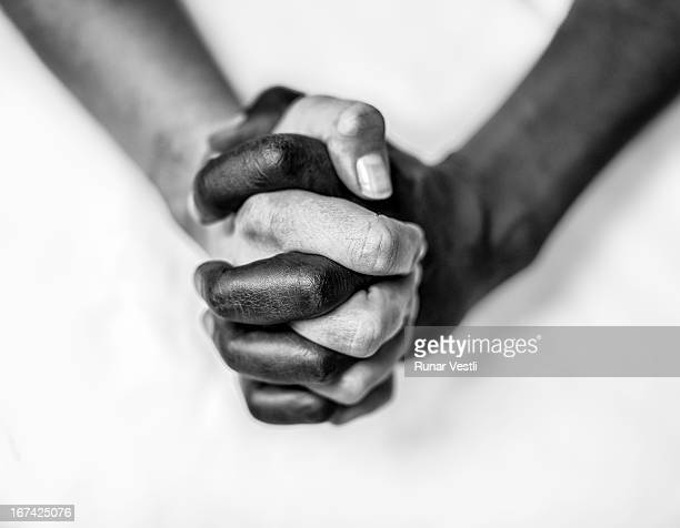Black and white hands folded together