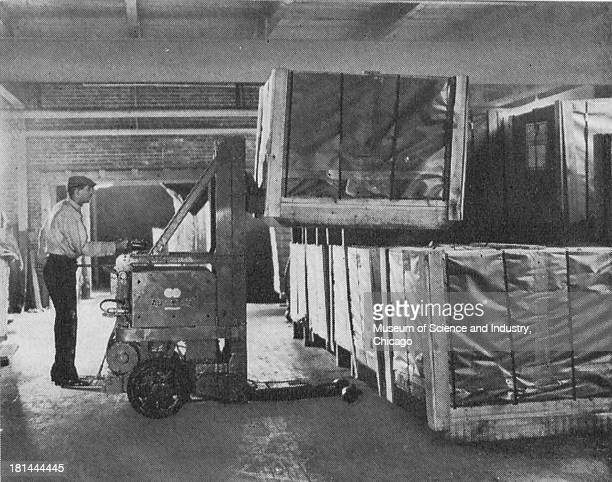 Black and white image of a man working with Type TLG 34 Low Platform Tiering Lifting Truck at a manufacturing warehouse which most manufacturers are...