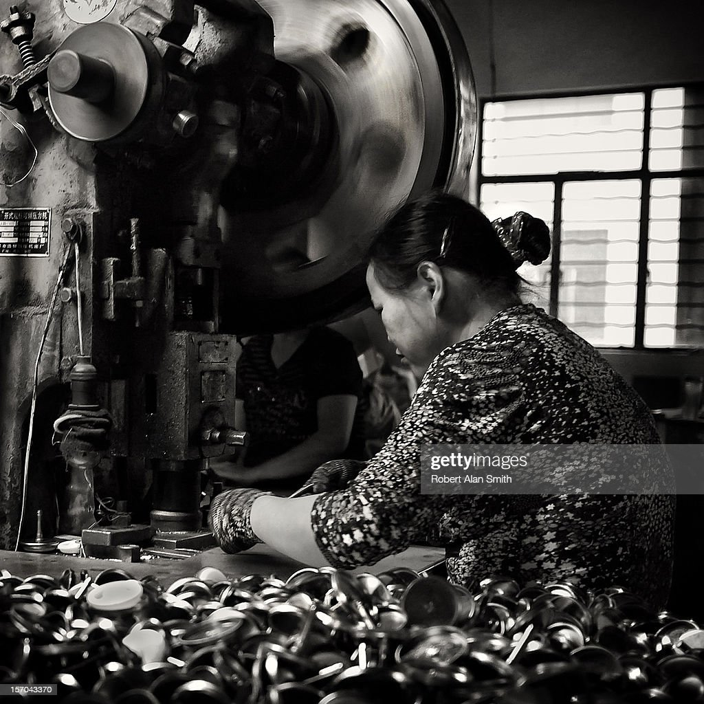 black and white image of a woman press operator making small components in a small factory in China. Press flywheel spinning with motion blur