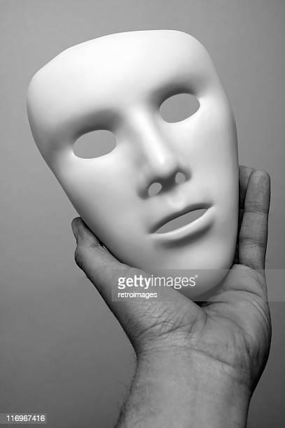 Immagine in bianco e nero di mano con Maschera da tragedia