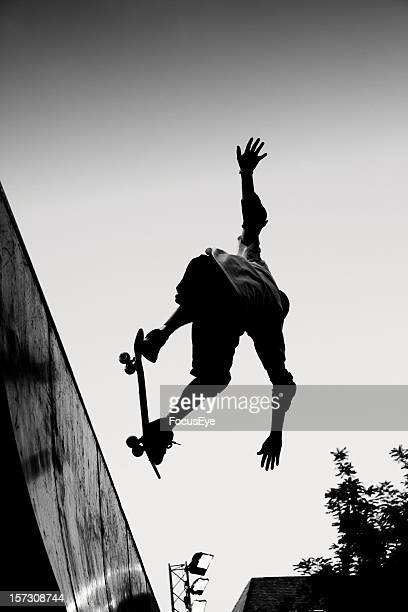 Black and white image of man performing a skateboard jump