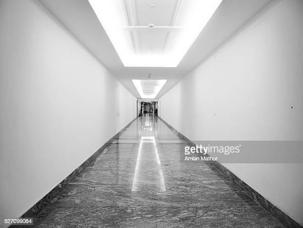 Black and white of a long gloomy corridor