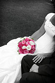 black and white of bride and groom with the pink bouquet highlighted and colored