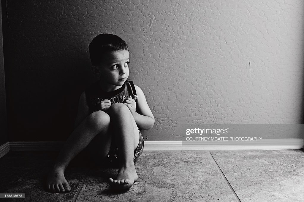 Black and White of young boy sitting on the floor : Stock Photo
