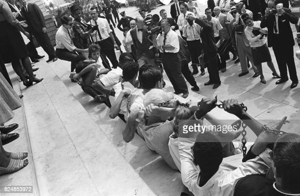 Black and white people chain themselves and sit in front of the New York City Hall on August 23 during a protest against segregation in some of...