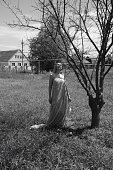 Black and white photo, a girl in the garden on a meadow in a dress.