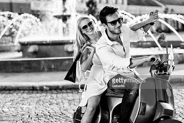 Black and white photo of a beatiful couple driving scooter