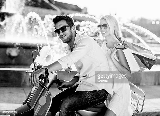 Black and white photo of a beautiful couple driving scooter