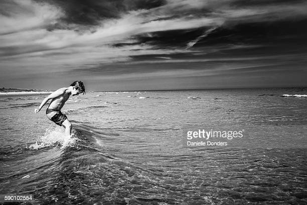 Black and white photo of a boy jumping over waves at the beach