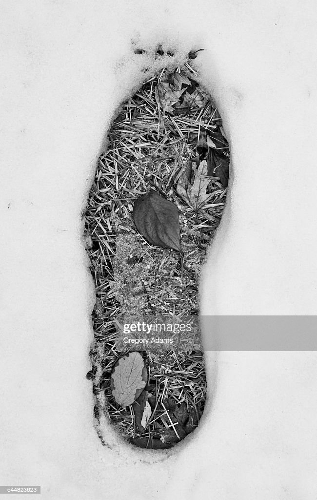 Black and white photo of a footprint in the snow