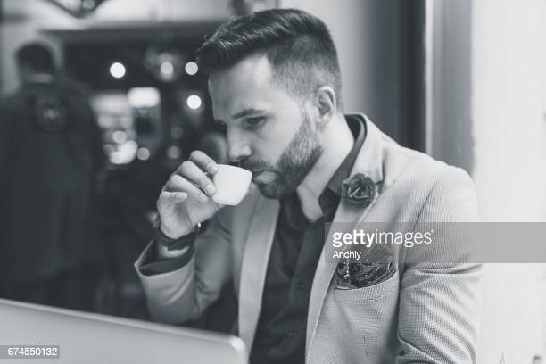 Black and white photo of a man drinking espresso in the bar