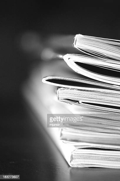 A black and white photo of a stack of magazines