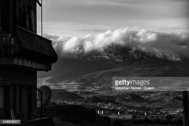 Black And White Photo Of Building Wall And Mountain Landscape With Dramatic Clouds