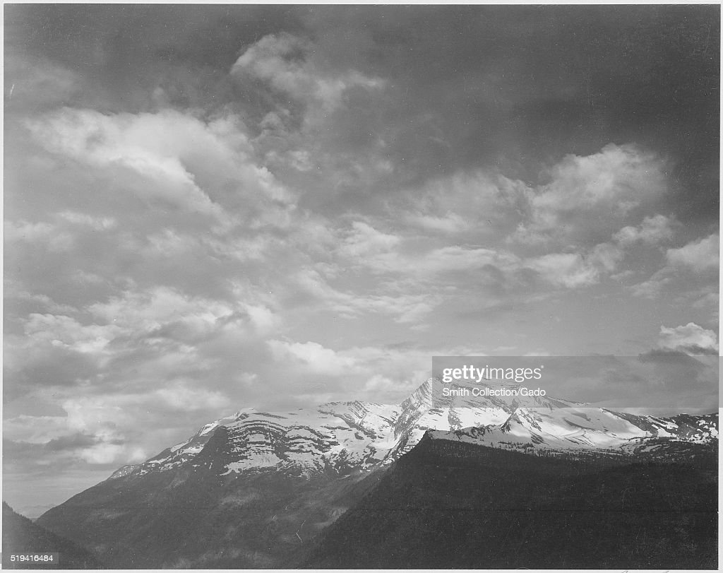 Black and white photograph dark foreground and clouds mountains highlighted captioned 'Heaven's Peak' by Ansel Adams from Photographs of National...