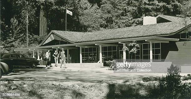 Black and white photograph featuring lodge surrounded by trees and nature